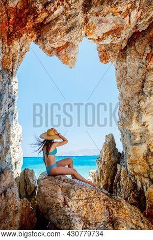 Cute girl enjoying breathtaking beach dotted with amazing sea caves on Greek island of Milos
