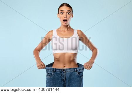 Shocked Skinny Woman Pulling Her Old Large Loose Jeans