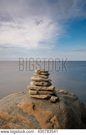 A Meditative Rock Cairn On Top Of A Boulder With Long Exposure Ocean And Sky In The Background