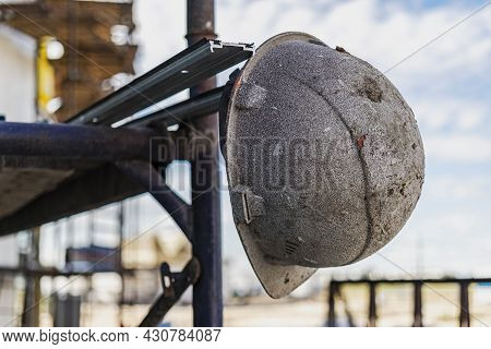 An Old Work Helmet Hangs On The Scaffolding. Blurred Background. Builder Hard Work Concept