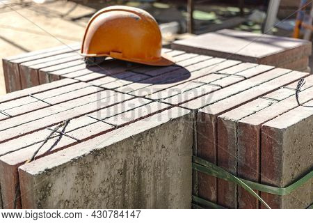 An Old Work Helmet Rests On Folded Paving Slabs. Rest Break At The Construction Site. Hard Work Of A