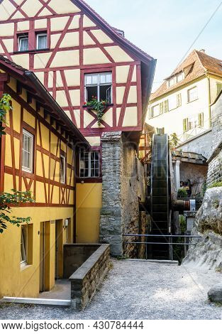Water Mill In Meersburg, Germany. Vertical View Of Old Half-timbered Houses And Medieval Mill Wheel.