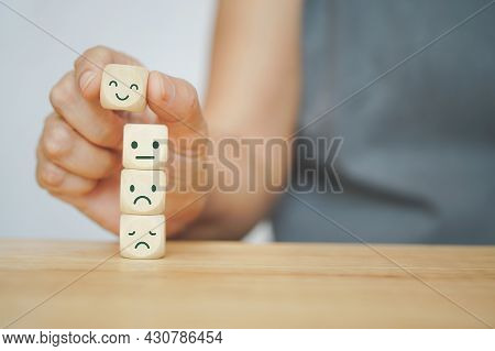 Senior Human Hand Selected Happy Face Wood Cube And Others On Green Background For Customer Service