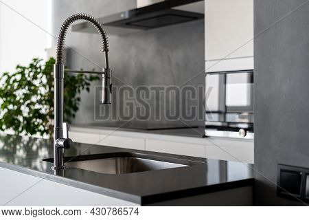 Modern Black And White Themed Kitchen With Light Coming From Window, Countertops With Sink And Fauce