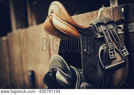 Brown And Black Saddles Hang On The Stall. Horse Ammunition. Equestrian Sport.