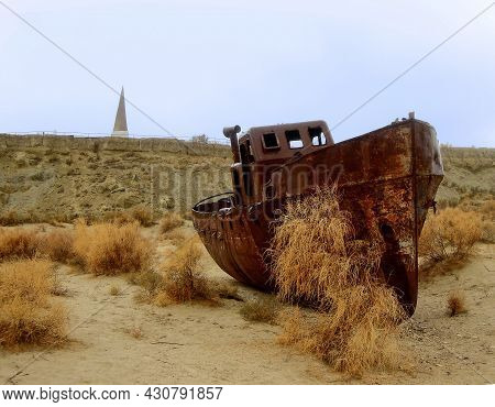 Rusty Remains Of Fishing Ship On The Dried Bottom Of The Former Aral Sea, And View On The Modern Sho