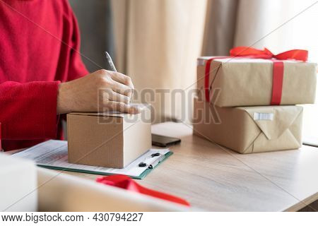 Close-up Of Male Hands Filling Out A Mailing Form On A Parcel Box In The Office Or At Home. Small Bu