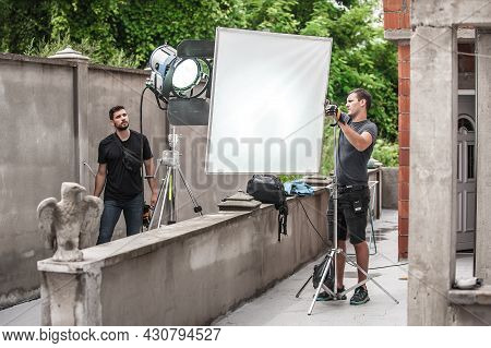 Behind The Scene. Filmmaking Lighting Technician Electric Engineer Adjusting And Setup Lights For Mo