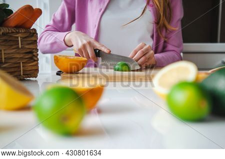 Beautiful Woman In Kitchen Slice Fruits For Juice. Vegetarian Food. Healthy Organic Vegan Food. Vega