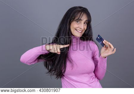 Beautiful Long-haired Brunette Woman In Her 40s, Smiling And Showing Her Credit Card.