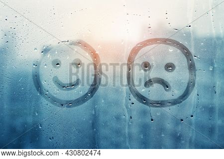 Sad Face And Happy Smile Doodle Painted On Window Flooded With Raindrops On Background Of City, Conc