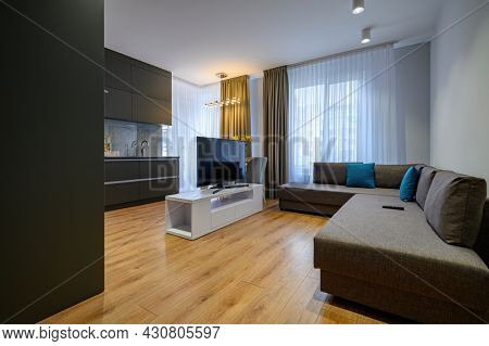 Modern trendy dark grey kitchen dining table and with TV set at the middle of room
