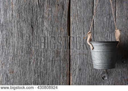 An empty metal pail hanging from twine against a rustic wood wall.