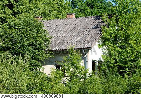 Abandoned Small White Suburban Family House With Destroyed Windows And Broken Window Blinds Covered