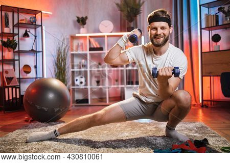 Smiling Bearded Guy Stretching Legs And Training Arms At Home. Caucasian Guy Using Dumbbells For Wor