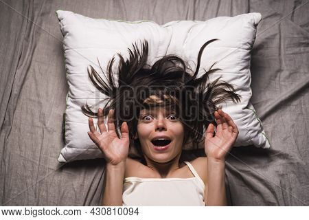 Young Girl With A Frightened Expression Wakes Up From A Nightmare In Bed. Woman Had A Terrible Unple