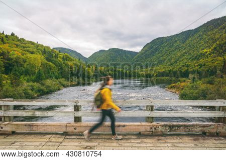Hiker woman with backpack walking on bridge crossing river. Motion blur of tourist hiking in outdoor nature fall. Autumn traveling hike in Quebec, Canada.