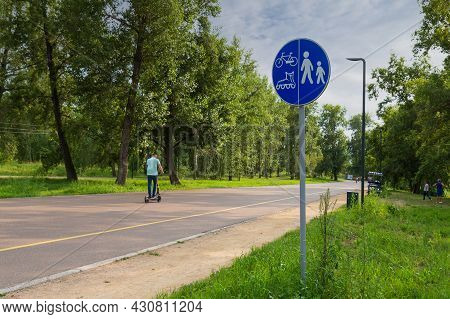 Blue Traffic Road Sign Separate Lanes For Pedestrians, Bikes And Roller Skates In Summer City Park