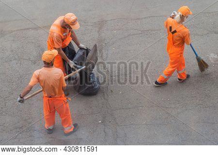 Krasnoyarsk, Russia - 19 August, 2021: Utilities Workers In Orange Uniforms With Scoops And Brooms S