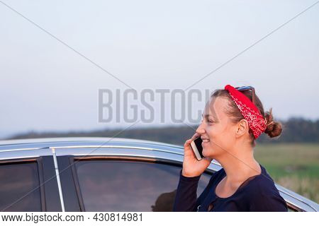 Pretty Woman In Bandana With Smartphone By Car Nature Background. Positive Confident Young Lady Smil