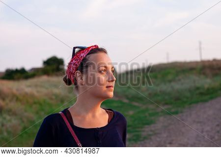 Pretty Hipster Woman In Red Bandana On Nature Background Autumn Sunset. Positive Confident Young Lad