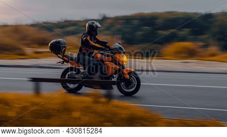 Motorcycle Kawasaki Er-6n In Motion On The Country Road In Evening. Side View Of Man Riding Motorbik
