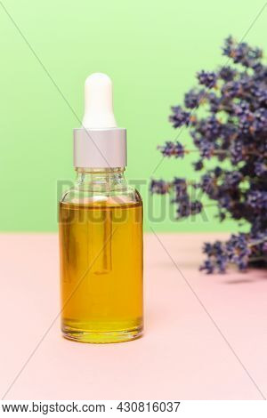Bottle Of Natural Organic Oil With Lavender Bouquet At The Background. Green Cosmetics To Moisturize