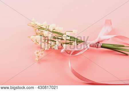 Lily Of The Valley Bouquet Tied With A Pink Ribbon On A Pink Background. Delicate Spring Concept