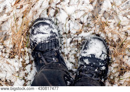 Snow-covered Black Boots Of A Man On His Feet While Walking In A Winter Park, Top View. Man In Black