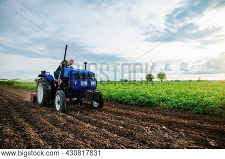 A Farmer Is Cultivating A Farm Field. Seasonal Worker. Recruiting Workers With Driving Skills Of Agr