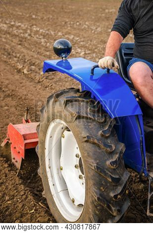The Tractor Is Cultivating The Soil In The Farm Field. Loosening And Mixing. Softening Of The Soil A