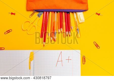 Pencil Box With Pens And Notebook With An Excellent Grade On A Yellow Background. Flat Lay. Concept