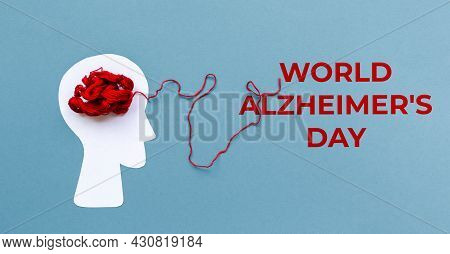 World Alzheimer's Day. Paper Silhouette Of Human Head With Red Tangled Threads On Blue Background. F