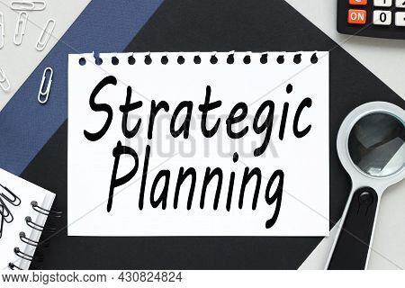 Business Strategic Planning. Text On White Notepad Paper On Gray And Black Background. Glasses And P