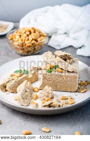 Pieces Of Sunflower And Peanut Halva And Mint Leaves On A Plate And A Bowl Of Nuts On The Table. Cal