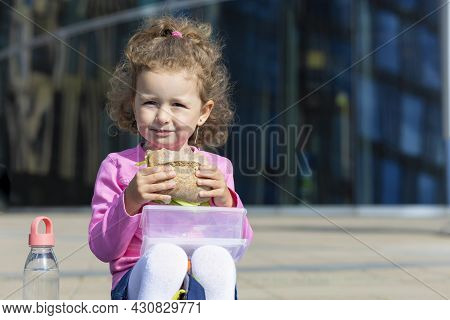 Hungry Cute Child With Appetite Eating Fast Food, Portrait. Happy Girl Biting Homemade Sandwich. Har
