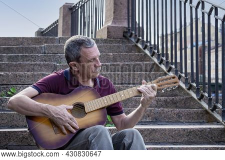 Adult Elderly Man Of Retirement Age Plays Old Six-string Classical Acoustic Guitar Outdoors While Si