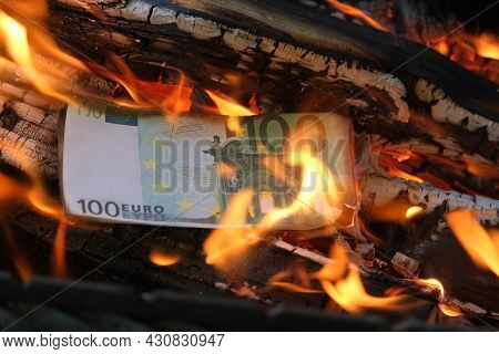 A 100 Euro Banknote Is Burning In A Flame Of Fire. Close-up, Horizontal Photo. Concept - Crisis, Def