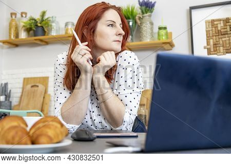 Smiling Red Haired Woman Sitting At The Table In Her Dining Room Drawing On A Tablet Computer With A