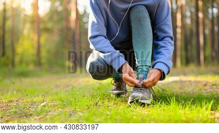 The Girl Ties Her Shoelaces And Prepares For A Morning Run In The Autumn Forest.