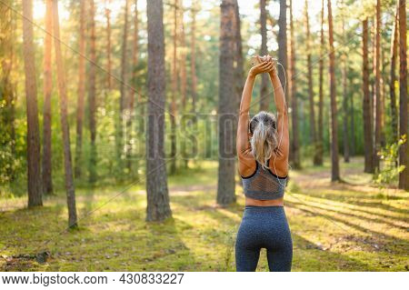 A Slender Athletic Girl Pulls Her Arms Up And Prepares For A Fitness Class In A Pine Forest. Selecti