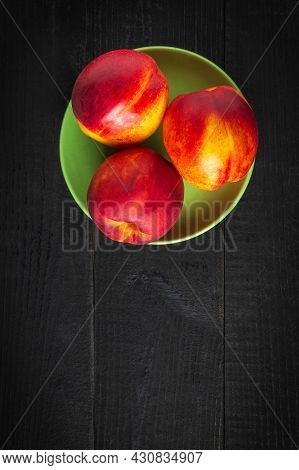 Three Red Ripe Nectarine Hybrids In Their Ripening Season Lie On Green Plate Or On A Dark Vintage Ta