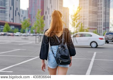Back View Of Walking Fashionable Teenage Girl With Backpack