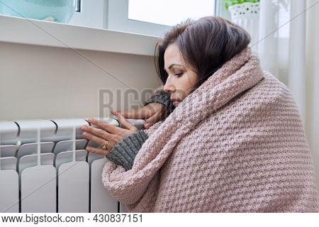 Winter, Heating Season. Woman In Warm Sweater Sitting In Home Room Near Heating Radiator