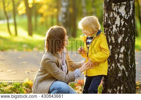 Little Boy With His Young Mother Having Fun During Stroll In The Public Park At Sunny Autumn Day. Ac