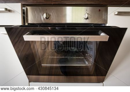 Selective Blur On The Open Door Of A Built In Integrated Electric Oven With Aluminum Stainless Steel