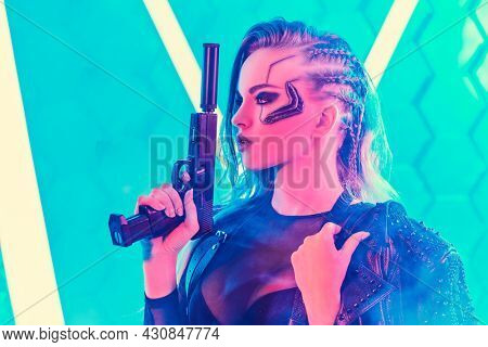 Sci-fi cyborg soldier girl. An attractive girl cyberpunk stands on alert with a gun among the neon lights. World of the future. Game, virtual reality.