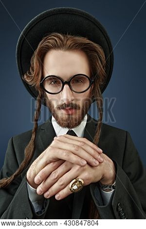 Portrait of a wealthy Jewish man with a gold ring on his finger looking at a camera. Rich Jew concept. Studio shot on a dark blue background.