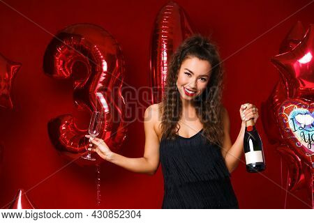 Happy Woman With Bottle Of Champagne On Red Background With Red Balloons. Cheerful Mood At The Holid