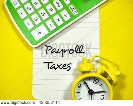 Business Concept.text Payroll Taxes Writing On Notepaper With Alarm Clock And Calculator On A Green